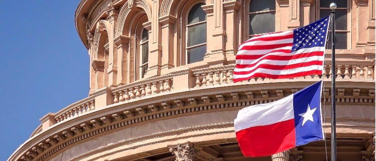 American flag with Texas flag at state capitol building in Austin: Shutterstock/CrackerClips Stock Media.