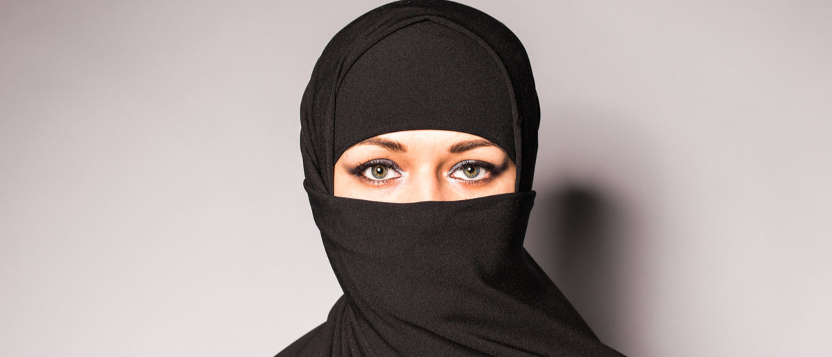Portrait of an arabic young woman with her beautiful blue eyes in traditional islamic cloth niqab. Shutterstock/Tatiana Chekryzhova