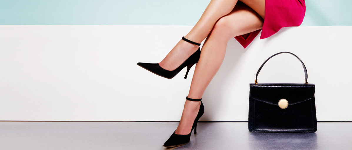 Shutterstock/ Beautiful legs woman wearing red dress with black purse hand bag with high heels shoes sitting on the white bench. with copyspace.