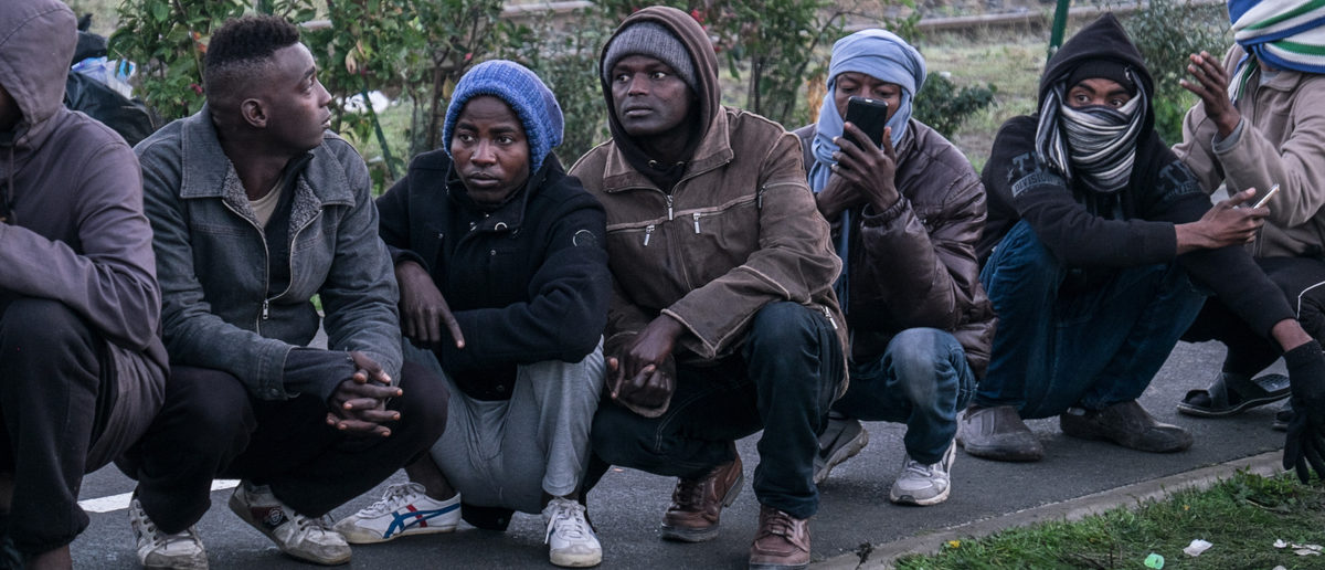 A group of migrants and refugees wait to leave the Jungle camp, Calais, France. November 2016. (Shutterstock)