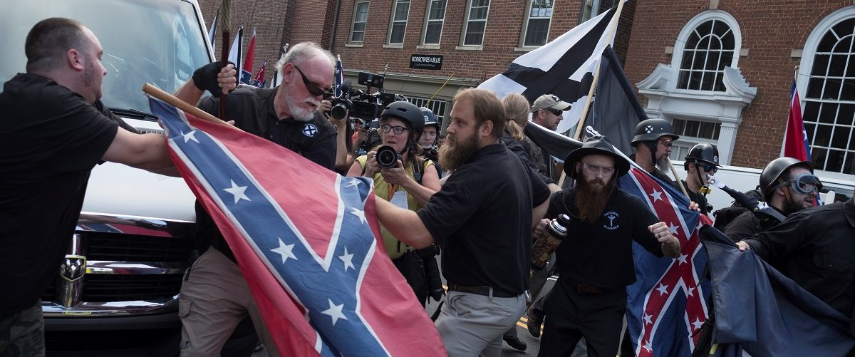 People struggle with a Confederate flag as a crowd of white nationalists are met by a group of counter-protesters in Charlottesville, Virginia, U.S., August 12, 2017.  REUTERS/Justin Ide - RTS1BIRV