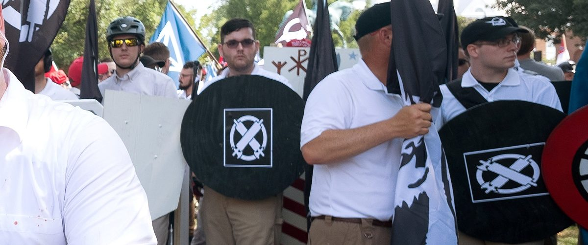 """James Alex Fields Jr., (2nd L with shield) is seen attending the """"Unite the Right"""" rally in Emancipation Park before being arrested by police and charged with charged with one count of second degree murder, three counts of malicious wounding and one count of failing to stop at an accident that resulted in a death after police say he drove a car into a crowd of counter-protesters later in the afternoon in Charlottesville, Virginia, U.S., August 12, 2017. Picture taken August 12, 2017 REUTERS/Eze Amos."""