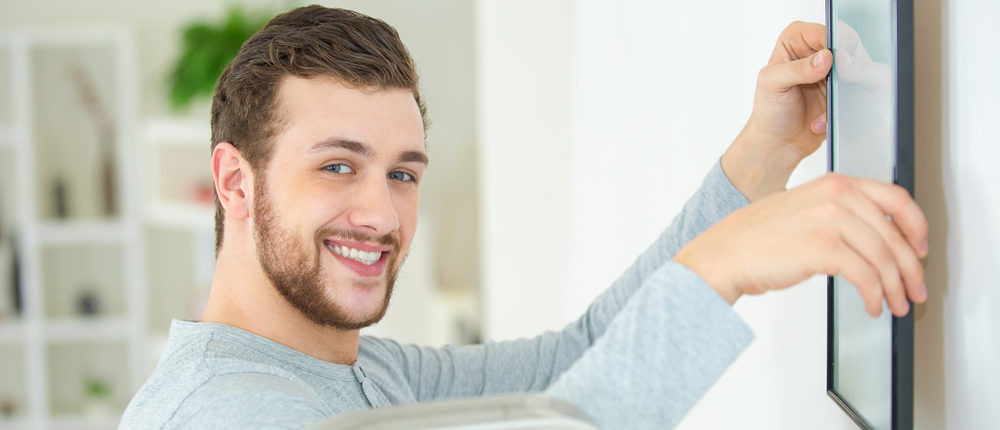 This is a happy man positioning a picture frame on a wall (Photo via Shutterstock)