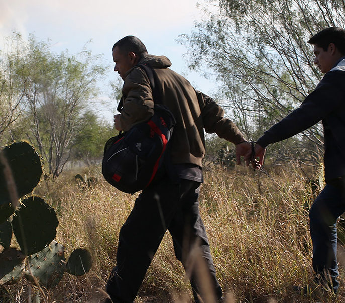 Immigrants walk handcuffed after illegally crossing the U.S.-Mexico border and being caught by the U.S. Border Patrol on December 7, 2015 near Rio Grande City, Texas. Border Patrol agents continue to capture hundreds of thousands of undocumented immigrants, even as the total numbers of those crossing has gone down. (Photo by John Moore/Getty Images)