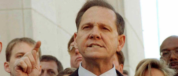 Alabama Chief Justice Roy Moore faces the media after being removed from office in Montgomery, Alabama, November 13, 2003. The nine members of Alabama's Court of the Judiciary unanimously voted to remove Moore, whose refusal to obey a U.S. order to move a Ten Commandments monument fueled a national debate over the place of God in public life. REUTERS/Bob Ealum