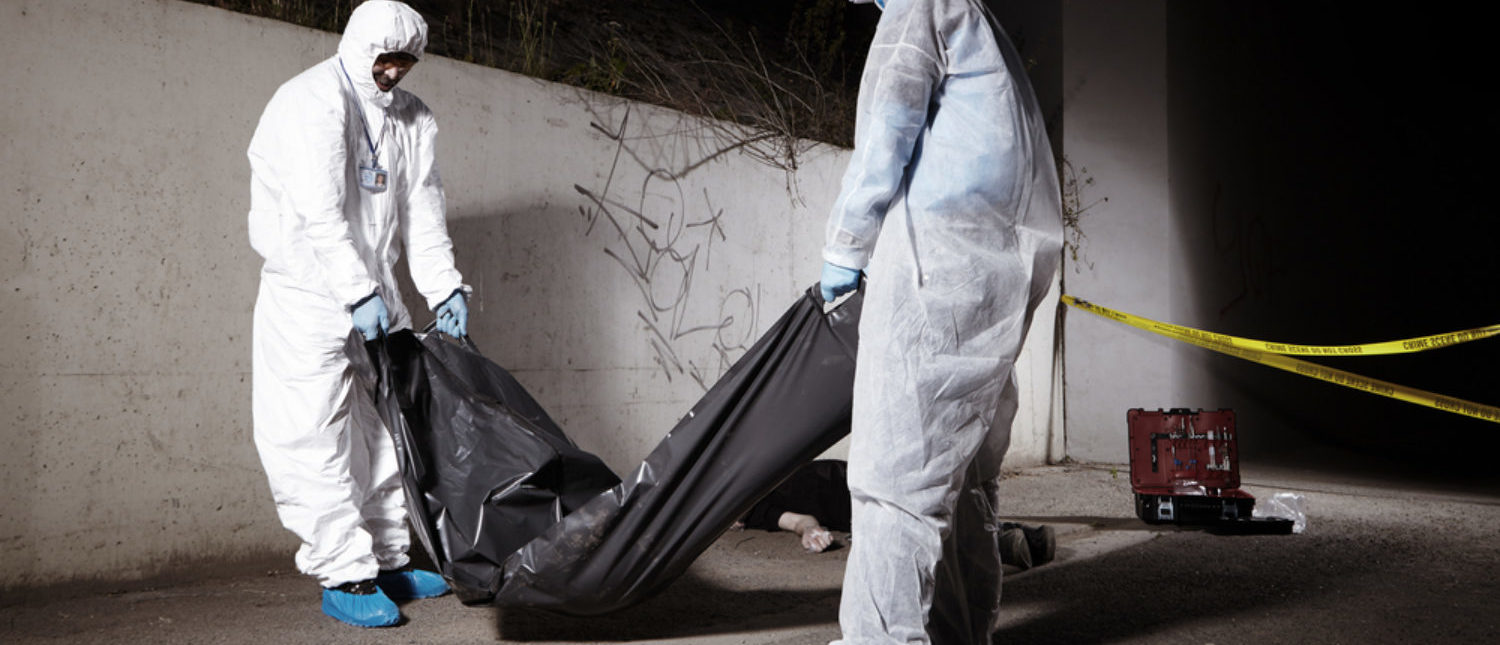 First responders and criminology technicians placing a body in a bag and taking it off the premises of the crime scene. [Shutterstock - Couperfield]