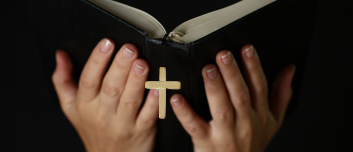 Female hands holding an open Bible with a crucifix.The concept of religion.. Credit: Studio KIWI/Shutterstock)