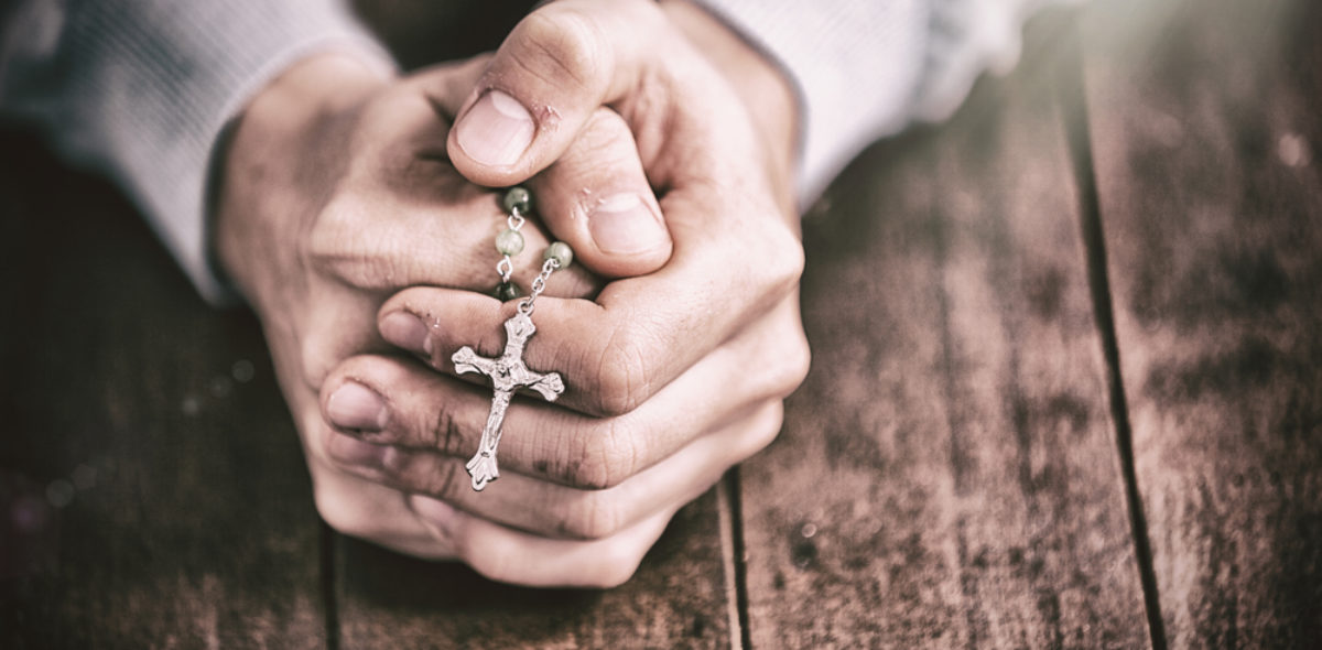 Man praying with rosary on wooden desk (vectorfusionart/shutterstock_675133354)