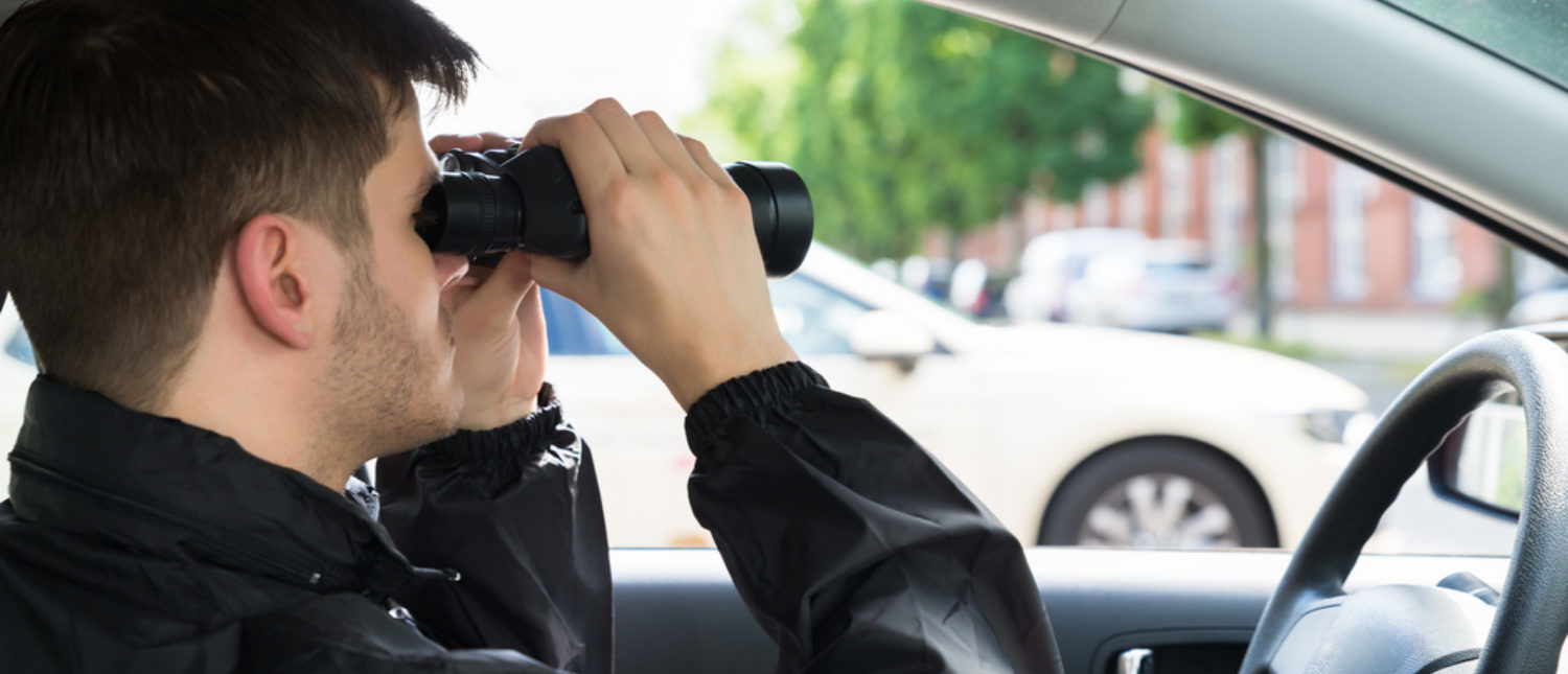 Man inside his car looking at people through his binoculars. [Shutterstock -  Andrey_Popov]