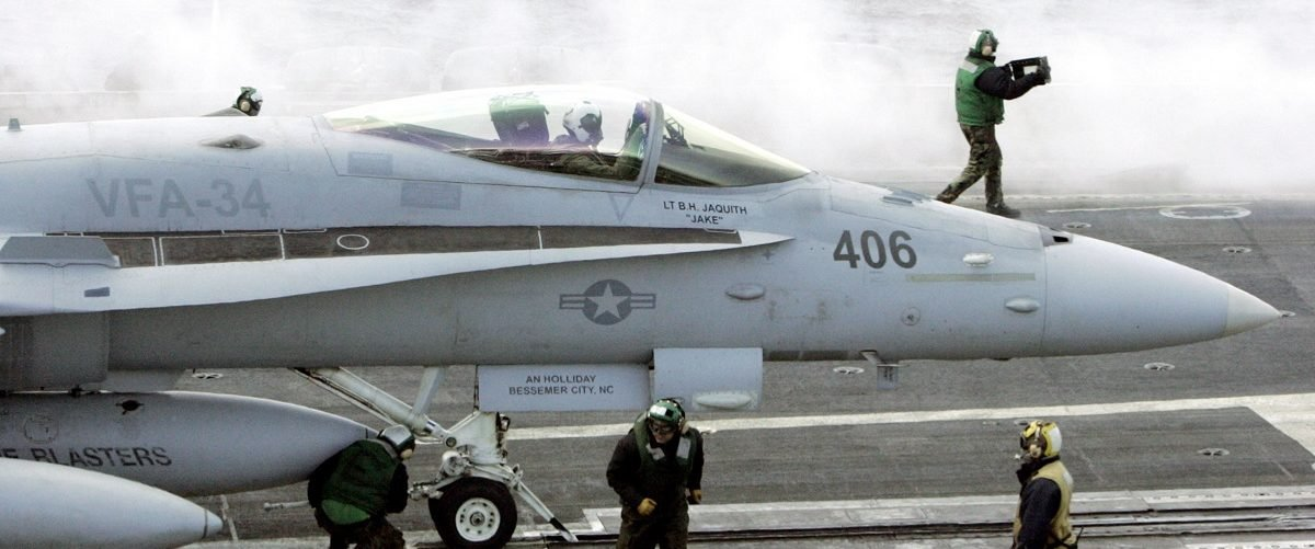 U.S. Navy crew members prepare for a F-18 Super Hornet's launch on the flight deck of the U.S. Navy carrier USS Abraham Lincoln off Ulsan