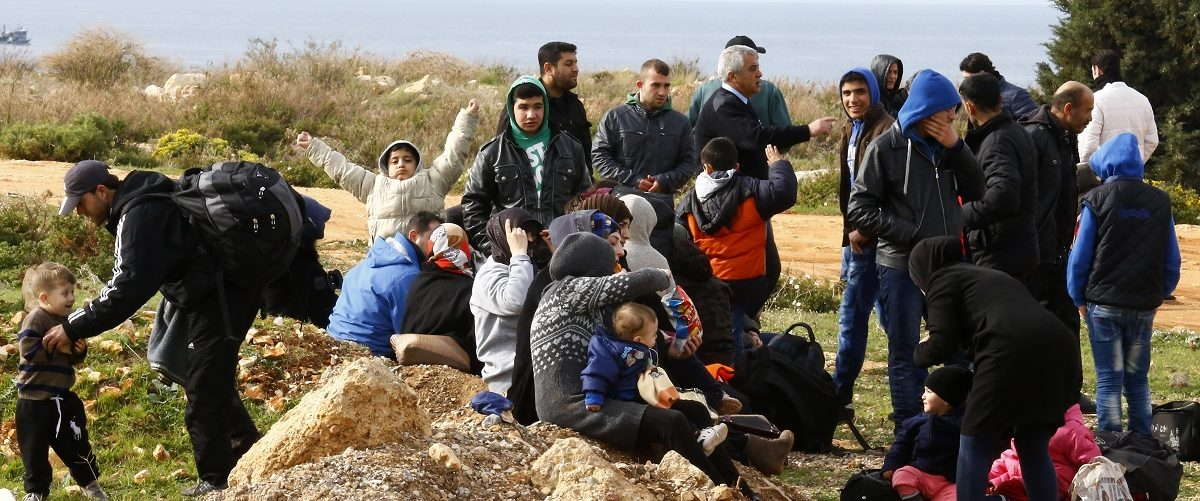 Syrian refugees wait on a roadside after Turkish police prevented them from sailing off to the Greek island of Farmakonisi by dinghies, near a beach in the western Turkish coastal town of Didim