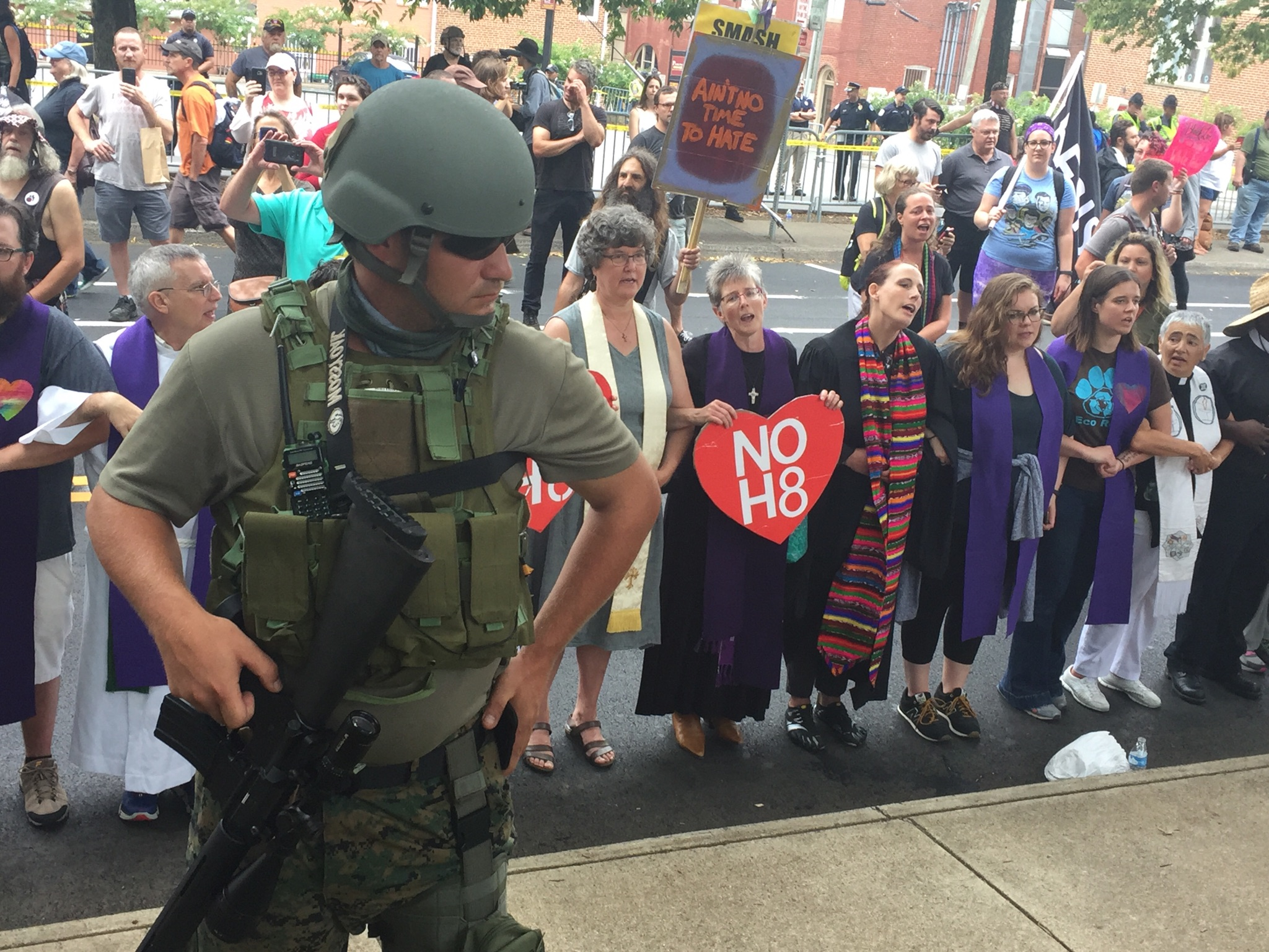 "A state militia member watches as faith leaders sing ""this little light of mine"" over his shoulder. (Henry Rodgers, TheDCNF)"