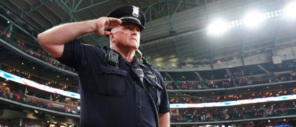 A Houston Police Officer salutes during a moment of silence at Minute Maid Field before the Houston Astros play the New York Mets in the first game after Tropical Storm Harvey in Houston, Texas, U.S., September 2, 2017. REUTERS/Carlo Allegri