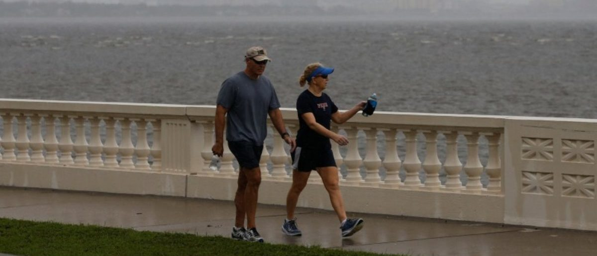 The Tampa skyline is seen in the background as people walk along Bayshore Boulevard ahead of the arrival of Hurricane Irma in Tampa, Florida, U.S., September 10, 2017. REUTERS/Chris Wattie