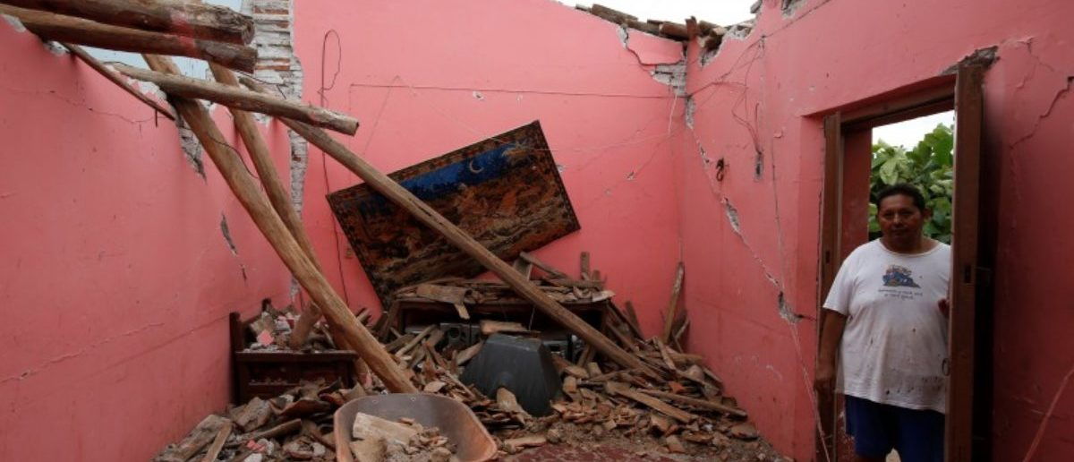 Humberto Cruz stands inside his house destroyed by the earthquake that struck the southern coast of Mexico late on Thursday, in Ixtaltepec