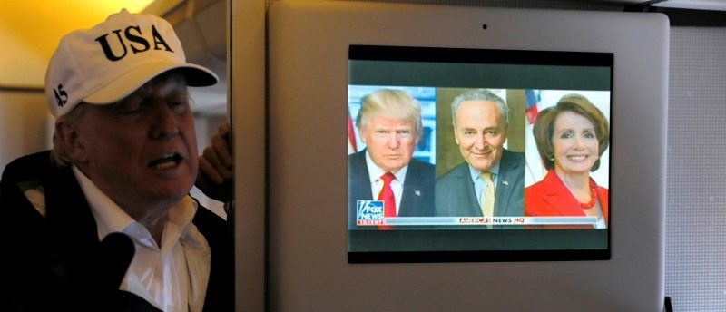 A news report about U.S. President Donald Trump's relationship with Senate Minority Leader Charles Schumer (D-NY) and House Minority Leader Nancy Pelosi (D-CA) plays on a television as he speaks to reporters in the press cabin aboard Air Force One on his way to Washington after viewing damage from Hurricane Irma in Florida, U.S. September 14, 2017. REUTERS/Jonathan Ernst