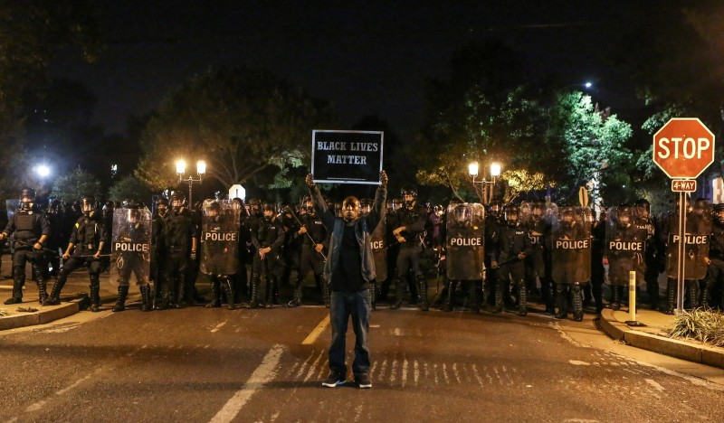 A Black Lives Matter protester stands in front of St. Louis Police Department officers equipped with riot gear after the not guilty verdict in the murder trial of Jason Stockley, a former St. Louis police officer, charged with the 2011 shooting of  Anthony Lamar Smith, who was black, in St. Louis, Missouri, U.S., September 15, 2017.  Photo taken September 15, 2017.  REUTERS/Lawrence Bryant