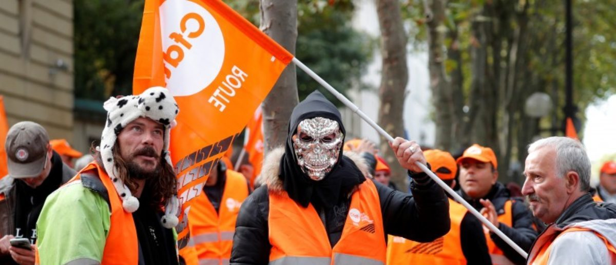 A masked demonstrator holds a flag of the French Democratic Confederation of Labour union (CFDT) in Paris during a national protest of lorry drivers against the government's labour reforms, France, September 18, 2017. REUTERS/Charles Platiau