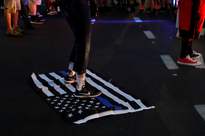"""A protester stands on a """"Blue Lives Matter"""" flag after the not guilty verdict in the murder trial of Jason Stockley, September 15, 2017. REUTERS/Whitney Curtis"""