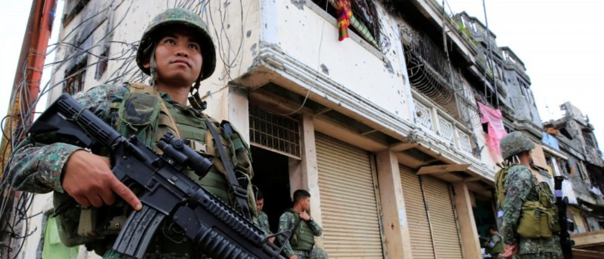 Government soldiers stand guard in front of damaged building and houses in Sultan Omar Dianalan boulevard at Mapandi district in Marawi city, southern Philippines September 13, 2017. REUTERS/Romeo Ranoco