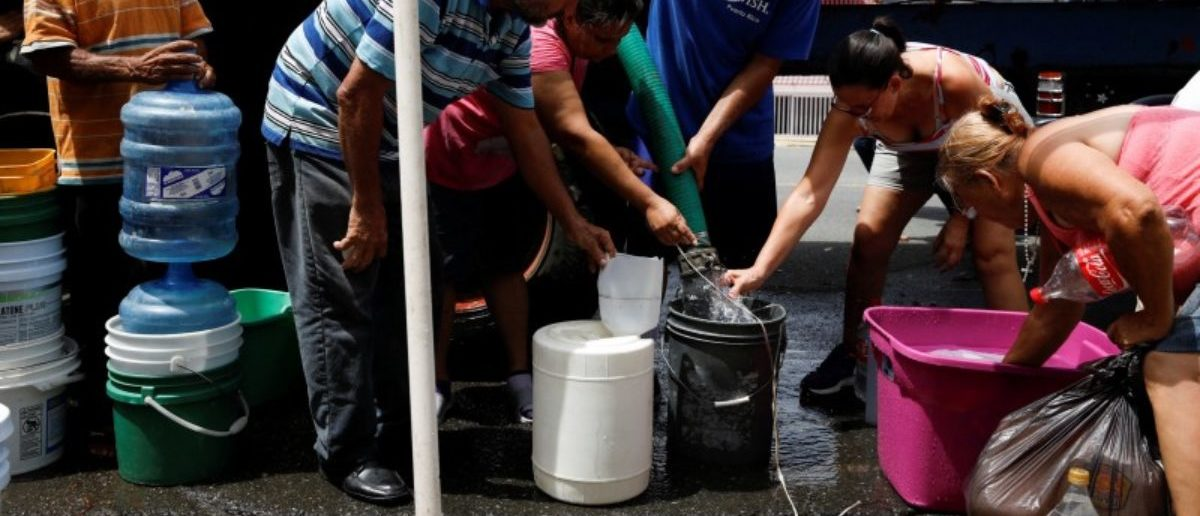 People queue to fill containers with water from a tank truck at an area hit by Hurricane Maria in Canovanas, Puerto Rico, September 26, 2017. Picture taken on September 26, 2017. REUTERS/Carlos Garcia Rawlins