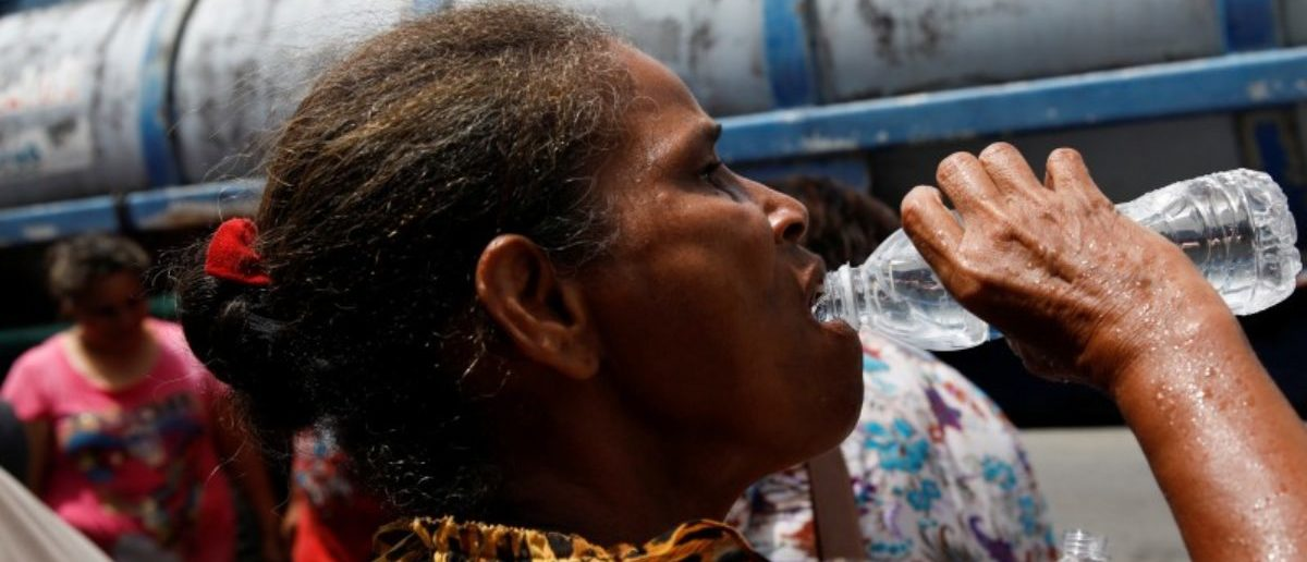 A woman drinks from a bottle after filling it with water from a tank truck at an area hit by Hurricane Maria in Canovanas