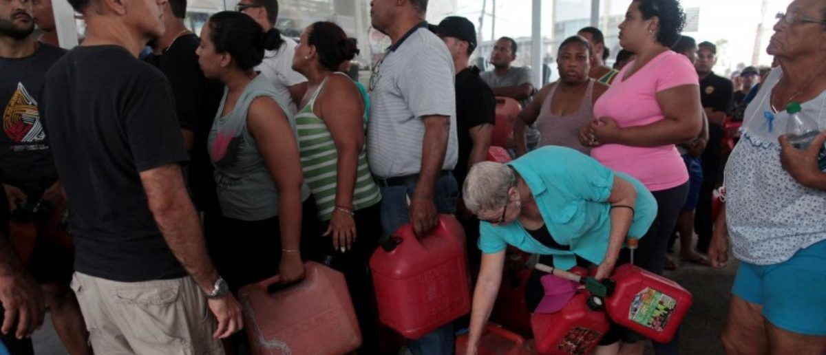 FILE PHOTO: People line up to buy gasoline at a gas station after the area was hit by Hurricane Maria, in San Juan, Puerto Rico September 22, 2017. Picture taken September 22, 2017. REUTERS/Alvin Baez/File Photo