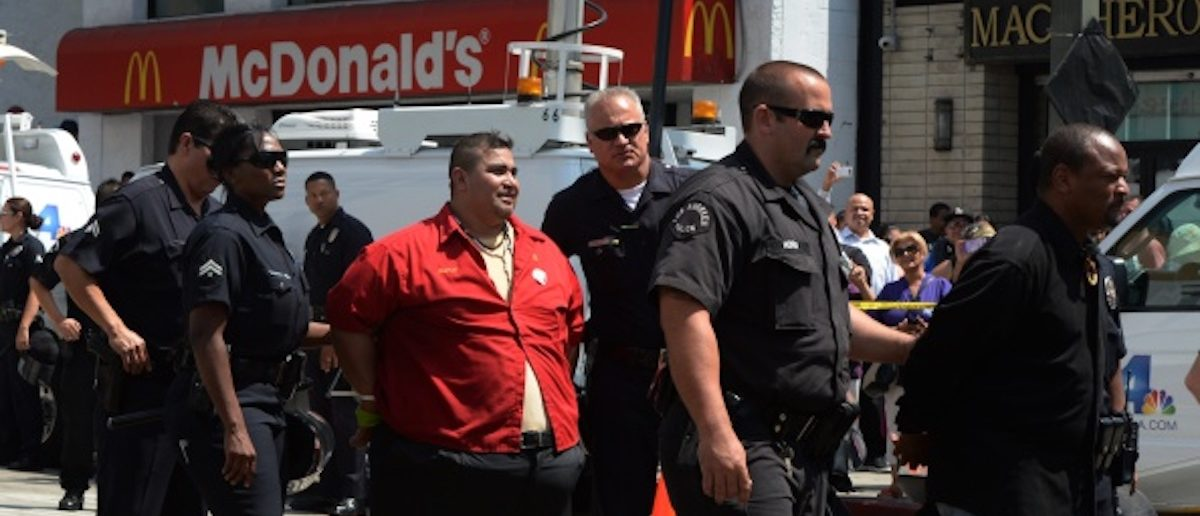 A fast food worker is detained by Los Angeles police after staging a sit-in outside a McDonald's restaurant during a demonstration against low wages in Los Angeles on September 04, 2014. A dozen protesters were arrested during the demonstration which is part of a series of nationwide protests calling for higher wages for fast-food restaurant workers. AFP PHOTO/Mark RALSTON (Photo credit should read MARK RALSTON/AFP/Getty Images)