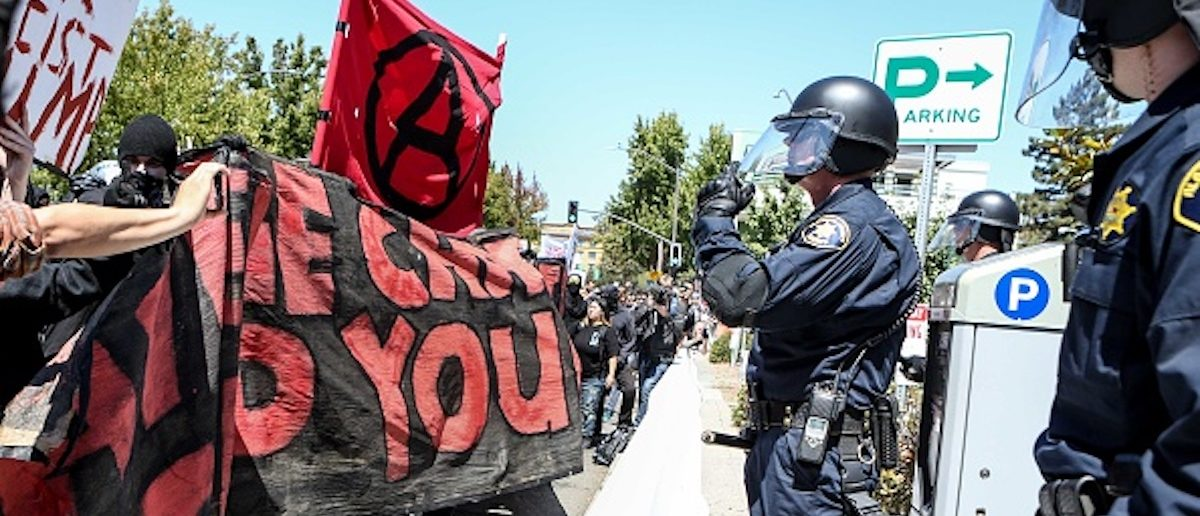 Riot police stand before Antifa members and counter protesters during a rightwing No To Marxism rally on August 27, 2017 at Martin Luther King Jr. Park in Berkeley, California. / AFP PHOTO / Amy Osborne (Photo credit should read AMY OSBORNE/AFP/Getty Images)