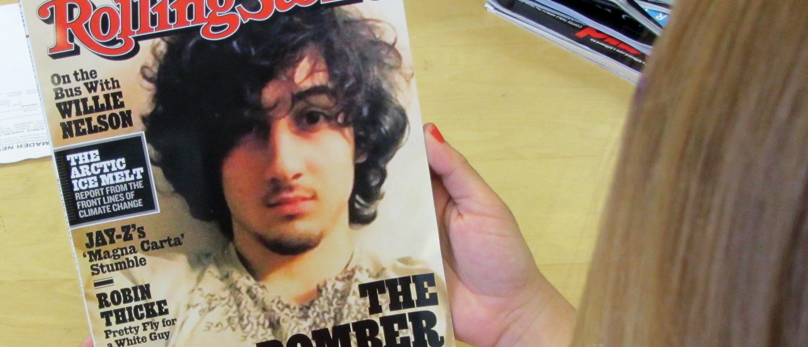 "An early copy of Rolling Stone magazine's August 2013 issue is read at an office in Los Angeles on July 17, 2013. Rolling Stone defended the cover story on Boston bombing suspect Dzhokhar Tsarnaev, which triggered criticism that the magazine was ""glamorizing terrorism"" and calls to boycott the publication. At least two national chain stores announced they would not be selling the latest issue of the magazine, known for interviews with rock stars and others. The cover picture -- showing a goateed Tsarnaev, 19, was likened to a famous Rolling Stone cover portrait of the late singer Jim Morrison of ""The Doors."" The accompanying Rolling Stones article, titled ""The Bomber,"" was described by the magazine as a ""deeply reported account of the life and times"" of Tsarnaev. The 12-page story is based on interviews with dozens of sources that ""deliver a riveting and heartbreaking account of how a charming kid with a bright future became a monster,"" it said. AFP PHOTO/Michael THURSTON (Photo credit should read Michael THURSTON/AFP/Getty Images)"