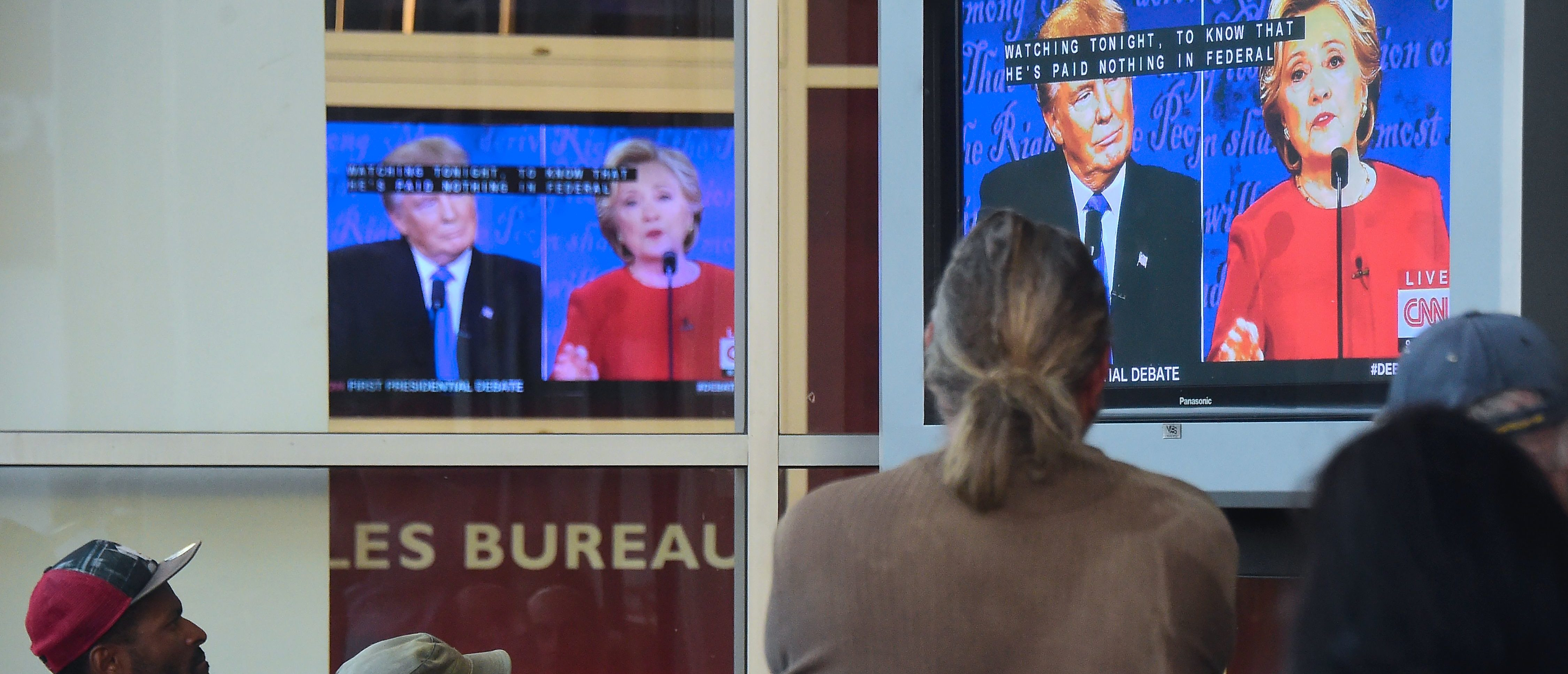 People gather to watch the first US presidential debate between Hillary Clinton and Donald Trump,nominees for the Democratic and Republican parties respectively, off a television set in front of an office building in Hollywood, California on September 26, 2016. FREDERIC J BROWN/AFP/Getty Images