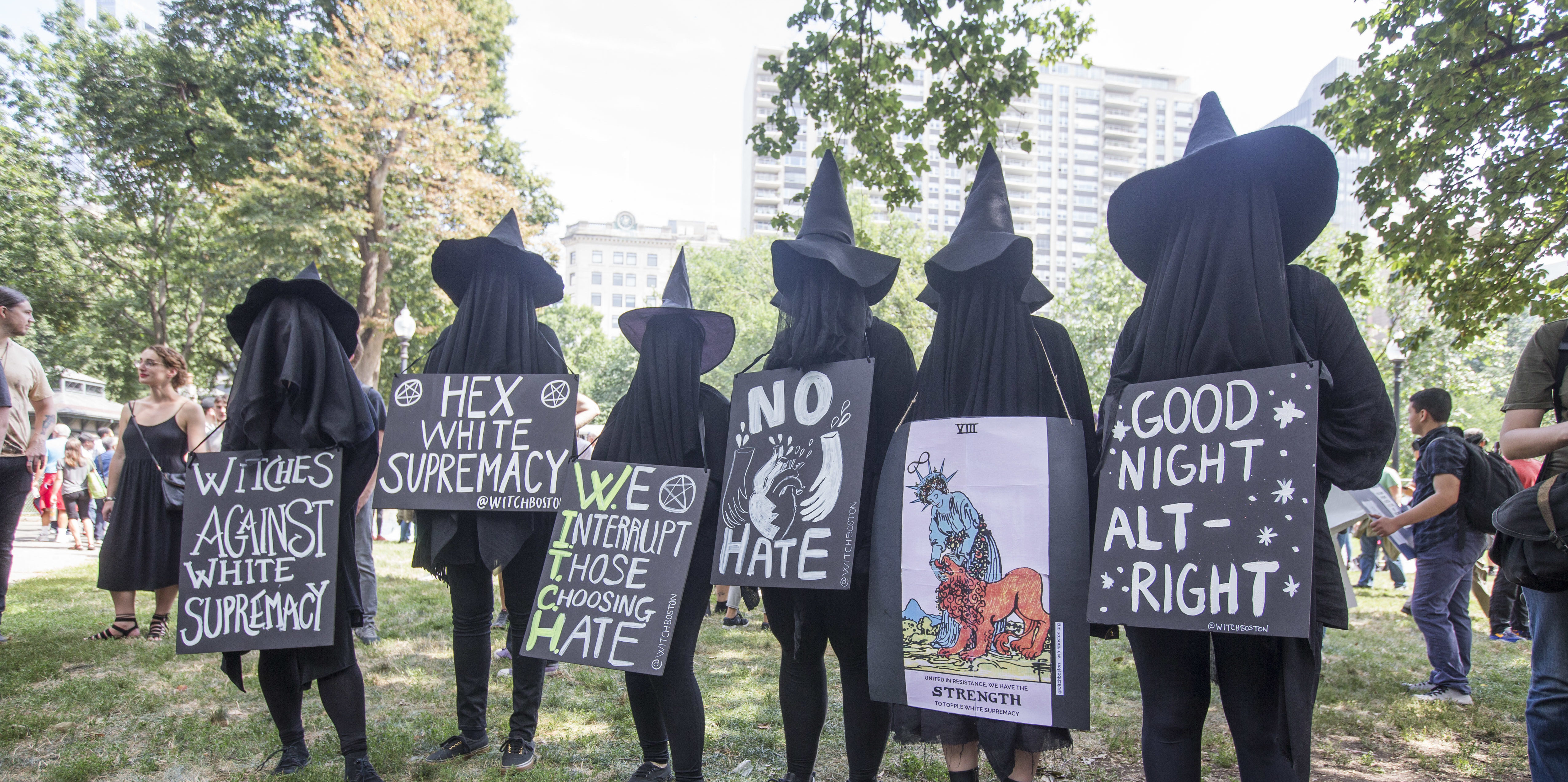 BOSTON, MA - AUGUST 19: Counter protesters in witch costumes hold up signs after a march to the 'Free Speech Rally' on Boston Common on August 19, 2017 in Boston, Massachusetts. Thousands of demonstrators and counter-protestors are expected at Boston Common where the Boston Free Speech Rally is being held. (Photo by Scott EisBOSTON, MA - AUGUST 19: Counter protesters in witch costumes hold up signs after a march to the 'Free Speech Rally' on Boston Common on August 19, 2017 in Boston, Massachusetts. Thousands of demonstrators and counter-protestors are expected at Boston Common where the Boston Free Speech Rally is being held. (Photo by Scott Eisen/Getty Images)en/Getty Images)