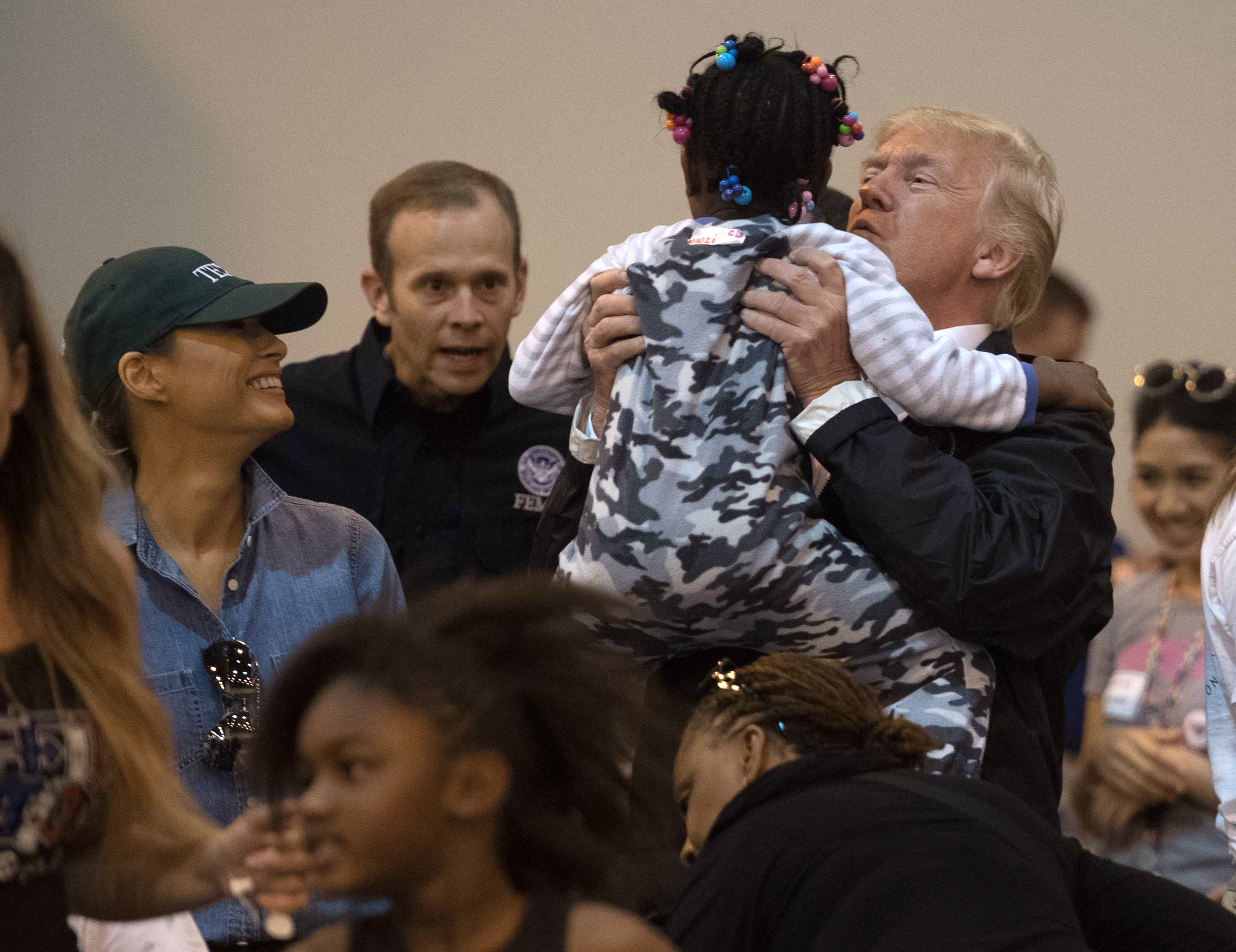 US President Donald Trump and First Lady Melania Trump greet a young Hurricane Harvey victim at NRG Center in Houston on September 2, 2017. NICHOLAS KAMM/AFP/Getty Images