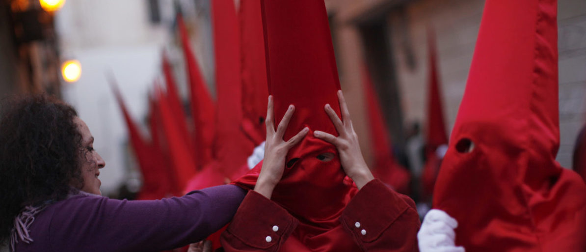 "A woman adjusts a ""Capirote"" hat on a penitent as he takes part in the Sangre brotherhood procession during Holy Week in Malaga, southern Spain April 4, 2012. Hundreds of processions take place around the clock in Spain during Holy Week, drawing thousands of visitors. REUTERS/Jon Nazca (SPAIN - Tags: RELIGION SOCIETY TPX IMAGES OF THE DAY) - GM1E8450IT301"