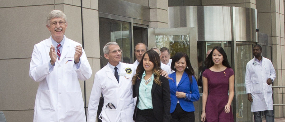NIH Director Dr. Francis Collins, (L), NIAID Director Dr. Anthony Fauci (2nd L) and NIH Clinical Center Director Dr. John Gallin (3rd L, rear) exit the NIH Clinical Center in Bethesda, Maryland with recently discharged Ebola patient Nina Pham in this October 24, 2014 handout photo. Pham, who contracted the disease while treating a man who later died of Ebola in a Dallas hospital, had been undergoing treatment at the National Institutes of Health in Bethesda, Maryland, since October 16. REUTERS/National Institutes of Health/Handout via Reuters (UNITED STATES - Tags: HEALTH) THIS IMAGE HAS BEEN SUPPLIED BY A THIRD PARTY. IT IS DISTRIBUTED, EXACTLY AS RECEIVED BY REUTERS, AS A SERVICE TO CLIENTS. FOR EDITORIAL USE ONLY. NOT FOR SALE FOR MARKETING OR ADVERTISING CAMPAIGNS - TM3EAAO186O01