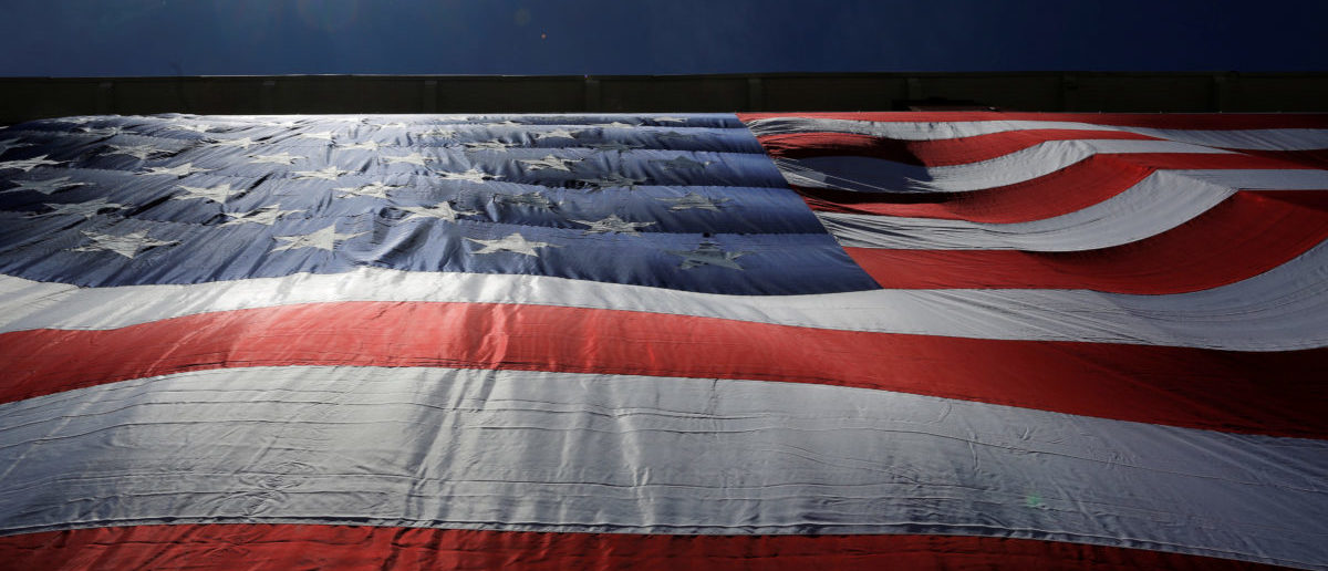 "As 95-by-50-foot American flag is unfurled on the side of an apartment complex, a replica of the ""The Great Flag"" that was spun, woven, dyed, constructed and displayed on the same building by Amoskeag Manufacturing Company in 1914, in Manchester, New Hampshire, U.S., June 14, 2017.   REUTERS/Brian Snyder"