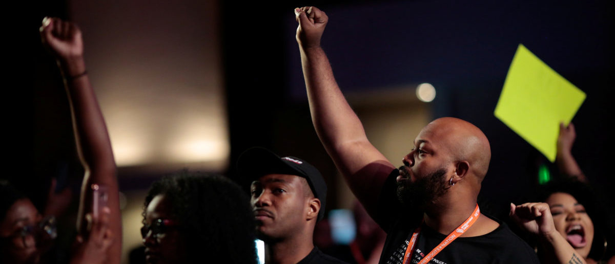 Ashton Woods (R), of Black Lives Matter:Houston, joins protesters as they disrupt a speech by Stacey Evans, who is running for governor of Georgia, at the morning plenary session at the Netroots Nation annual conference for political progressives in Atlanta, Georgia, U.S. August 12, 2017.  REUTERS/Christopher Aluka Berry