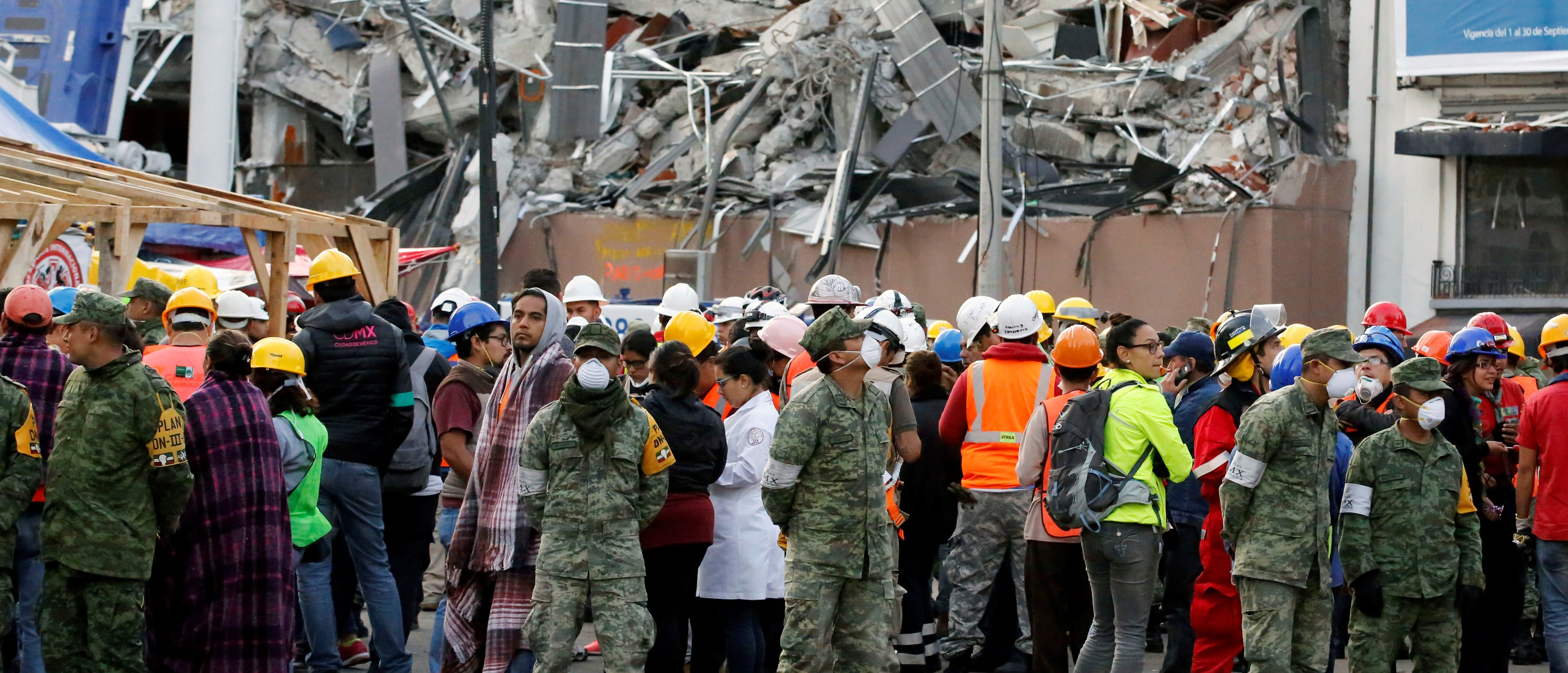 Soldiers and rescue team wait along the street after a tremor was felt in Mexico City, Mexico September 23, 2017. On background is pictured a collapsed building after an earthquake on September 19, 2017. REUTERS/Henry Romero