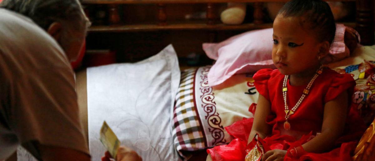 Devotees present offerings to the three year old chosen as Nepal's living goddess, or Kumari. Kathmandu, Nepal September 28, 2017. REUTERS/Navesh Chitrakar