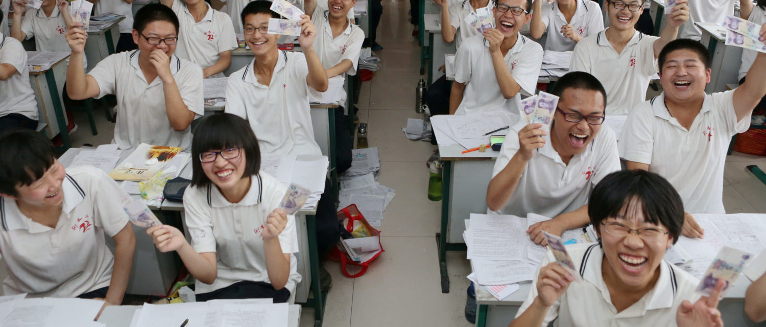 "Students hold and present 5 yuan banknotes as they pose to camera with their teacher at a classroom ahead of China's annual national college entrance exam or ""gaokao"" in Hengshui, Hebei Province, China, June 3, 2016. The school offers each student participating in the national college entrance exam two 5 yuan banknotes bearing serial numbers as souvenirs, which means good luck. REUTERS/Stringer ATTENTION EDITORS - THIS IMAGE WAS PROVIDED BY A THIRD PARTY. EDITORIAL USE ONLY. CHINA OUT. NO COMMERCIAL OR EDITORIAL SALES IN CHINA. - S1AETHXQRAAB"