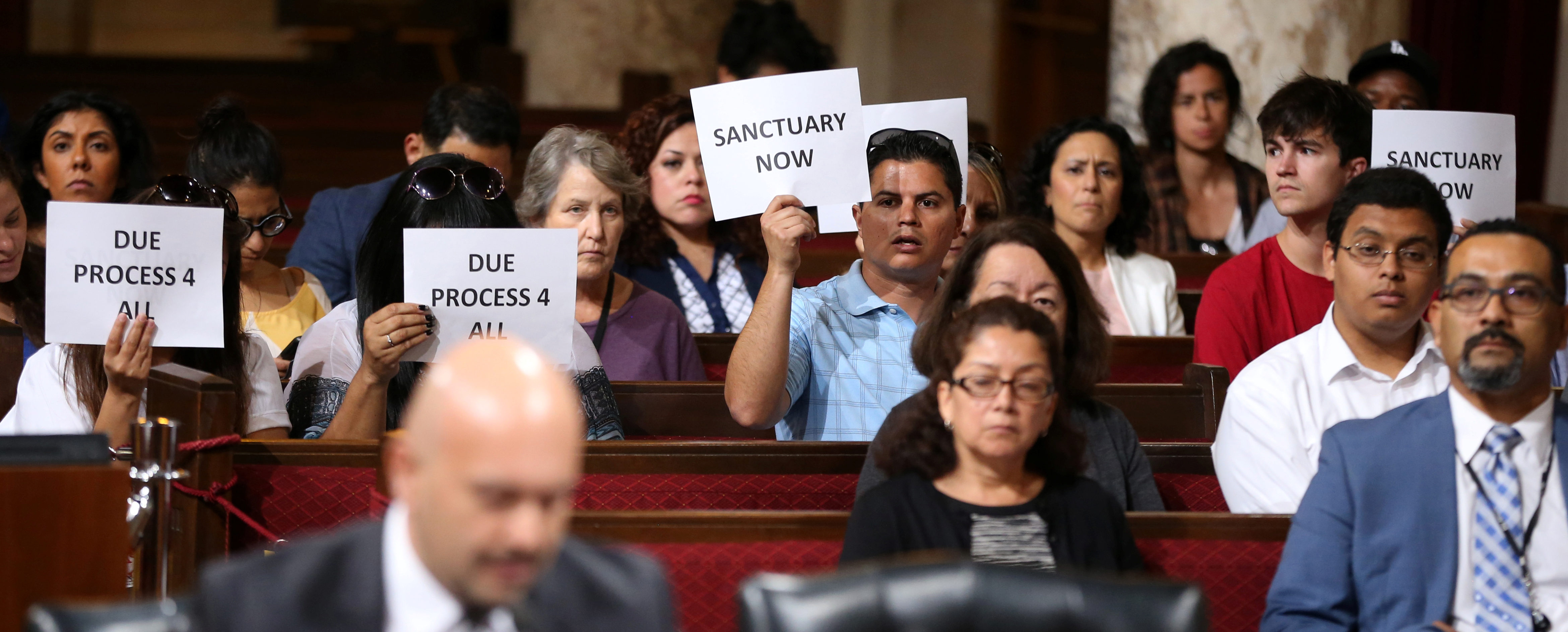 Immigrant supporters protest during the Los Angeles City Council ad hoc committee on immigration meeting to discuss the city's response to threats by the Trump administration to cut funding from Los Angeles and other jurisdictions which federal officials say are providing sanctuary to illegal immigrants arrested for crimes, in Los Angeles, California, U.S., March 30, 2017. REUTERS/Lucy Nicholson