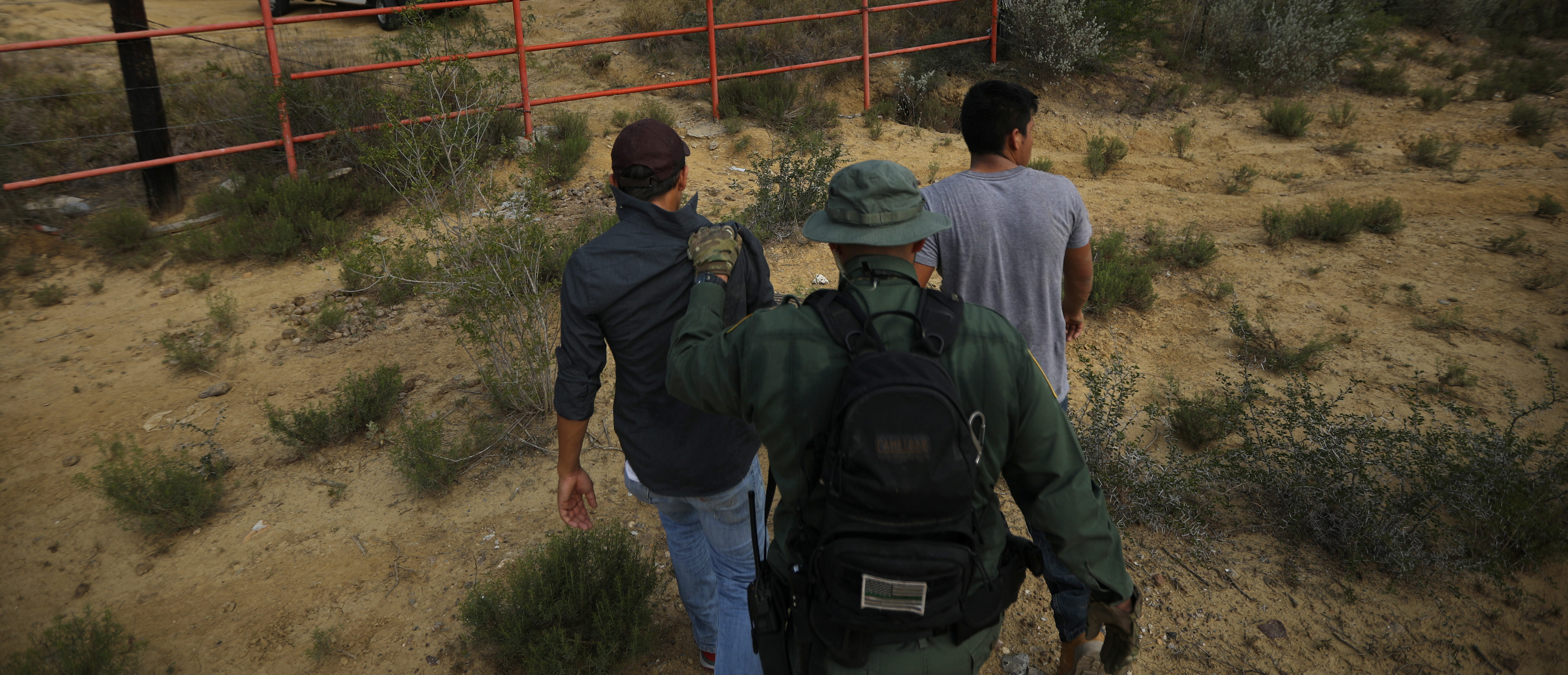 A U.S. border patrol agent escorts men being detained after entering the United States by crossing the Rio Grande river from Mexico, in Roma, Texas, U.S., May 11, 2017. REUTERS/Carlos Barria