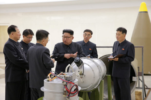 North Korean leader Kim Jong Un provides guidance with Ri Hong Sop and Hong Sung Mu on a nuclear weapons program in this undated