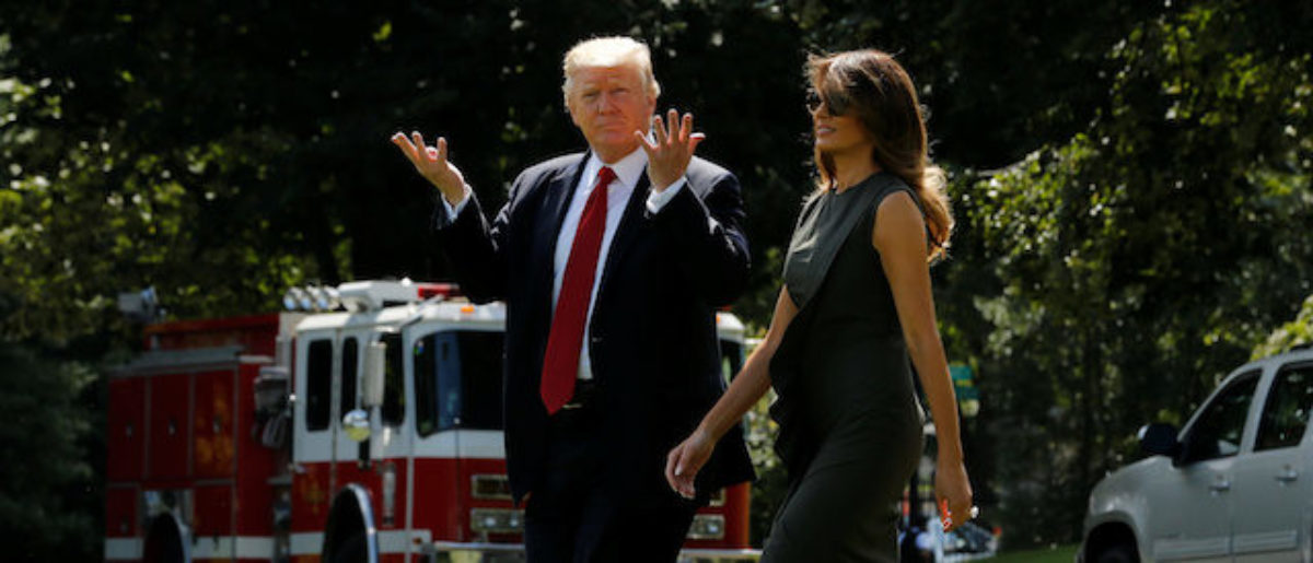 U.S. President Donald Trump signals to reporters that he can't hear their questions over the helicopter engines as he and first lady Melania Trump depart for a weekend retreat with his cabinet at Camp David, from the White House in Washington, U.S., September 8, 2017. REUTERS/Jonathan Ernst