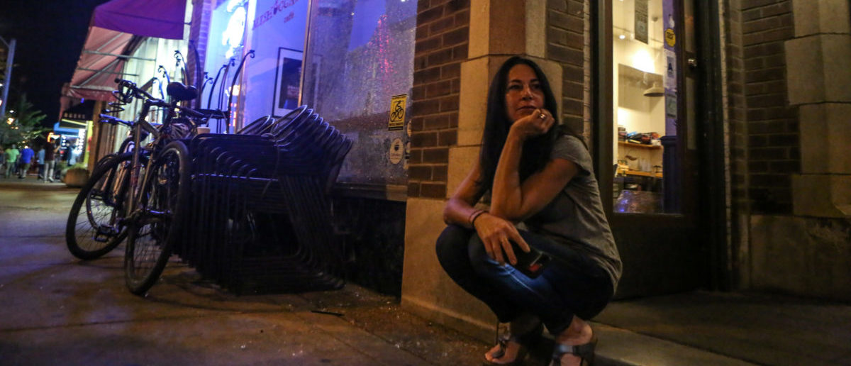 A store owner sits outside her shop after her front window was shattered by protesters during the second night of demonstrations after a not guilty verdict in the murder trial of former St. Louis police officer Jason Stockley, charged with the 2011 shooting of Anthony Lamar Smith, who was black, in St. Louis, Missouri, U.S., September 16, 2017. Photo taken September 16, 2017. REUTERS/Lawrence Bryant