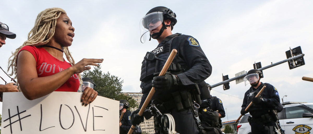 A woman says a prayer next to a police officer during protests after the not guilty verdict in the murder trial of Jason Stockley, a former St. Louis police officer charged with the 2011 shooting of Anthony Lamar Smith, in St. Louis, Missouri, U.S. September 17, 2017. Picture taken September 17, 2017. REUTERS/Lawrence Bryant