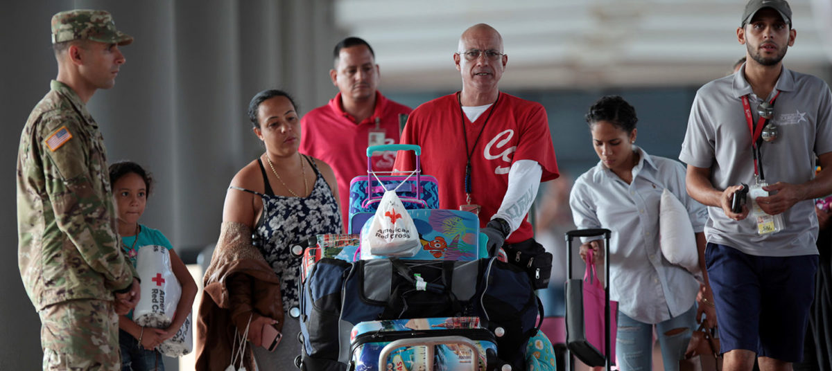 People push a luggage trolley after arriving along with other refugees onboard the Royal Caribbean's Majesty of the Seas cruise ship from St. Thomas, U.S. Virgin Islands, in San Juan, Puerto Rico September 14, 2017. REUTERS/Alvin Baez