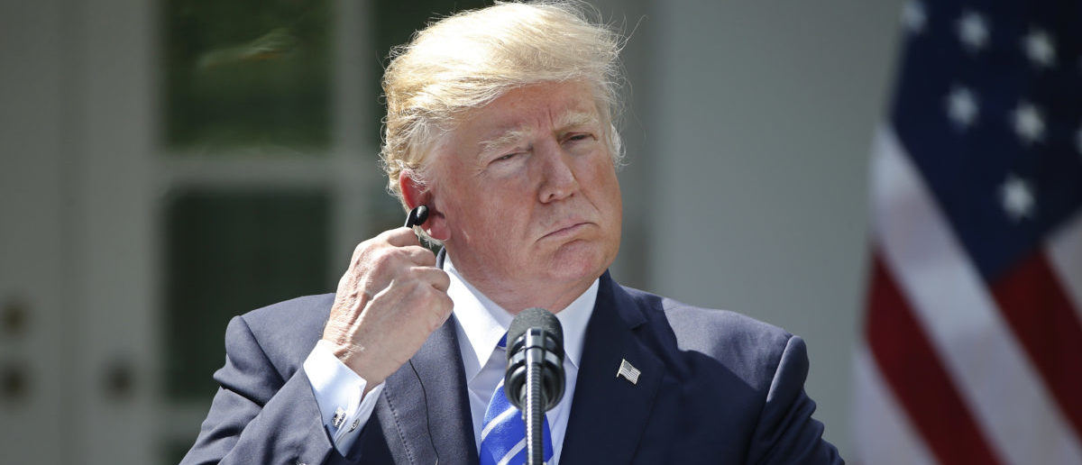 U.S. President Donald Trump removes his translation earphone as he holds a joint news conference with Spanish Prime Minister Mariano Rajoy in the Rose Garden at the White House in Washington, U.S., September 26, 2017. REUTERS/Joshua Roberts