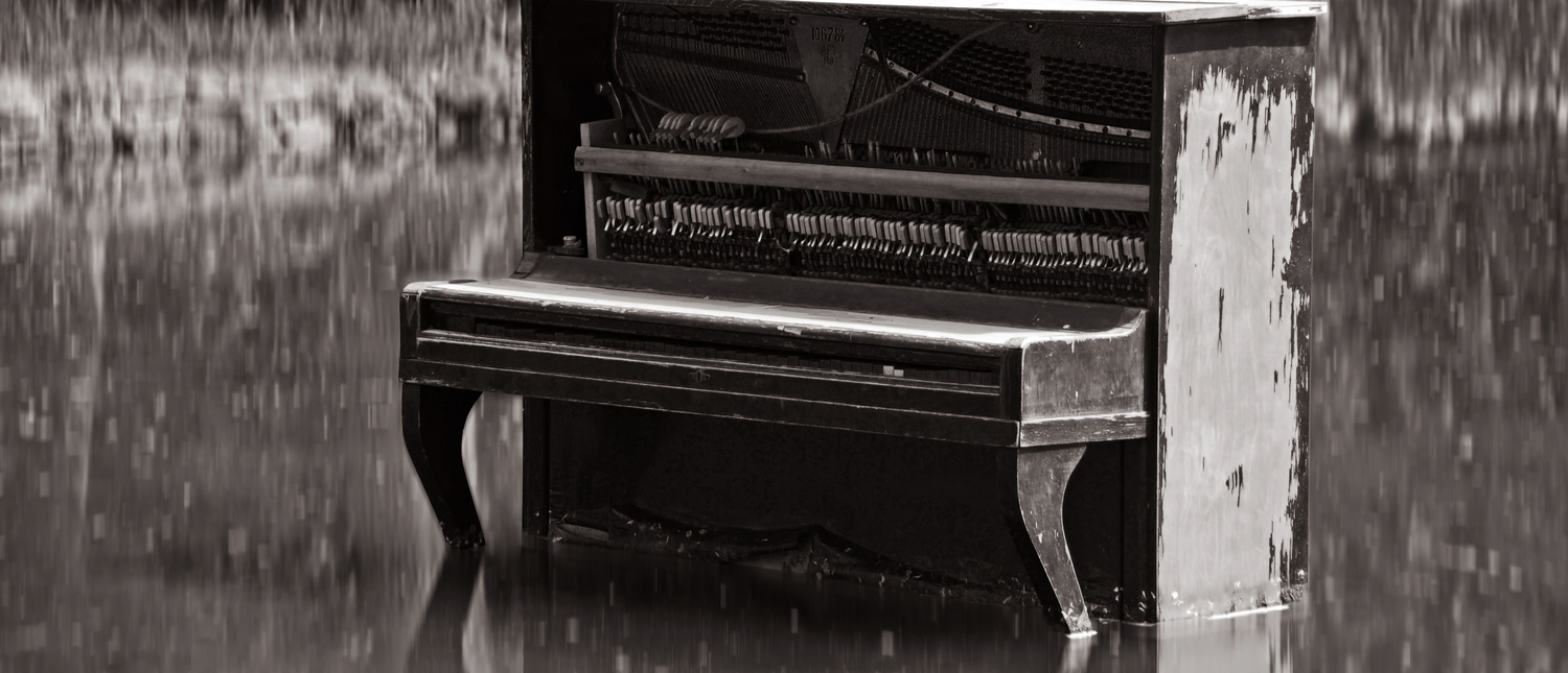Piano sits in flooded water (Photo: Shutterstock/Artem Avetisyan)
