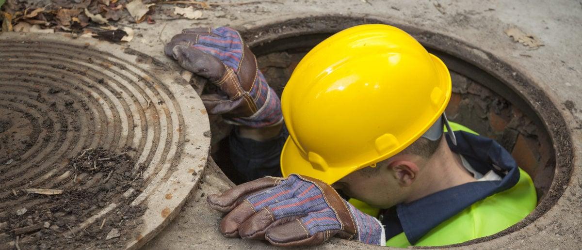 Manual worker inside manhole looking for the problem. (LightTheBox/Shutterstock)